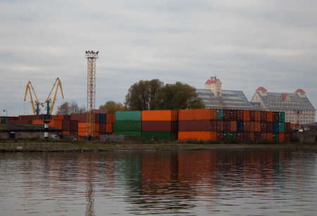 Containers with cargo in the port in the background of buildings at dawn