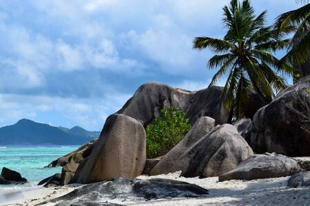 Blue Indian ocean, palm trees and autentical Seychelles rocks in Anse Source DArgent beach in La Digue island