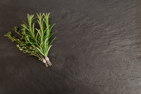 Thyme and rosemary bundles on black stone surface background 写真素材