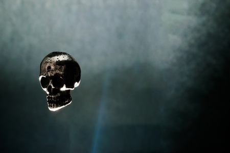 Metal skull levitating in air on black background illuminated by light. Mystical and spooky atmosphere