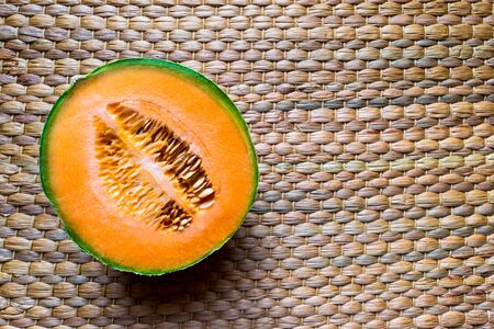 Cut ted in the half Hami melon fruit placed on brown straw mat background surface