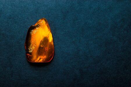 Ambersteen op donkerblauwe oppervlakte als achtergrond met vrije ruimte