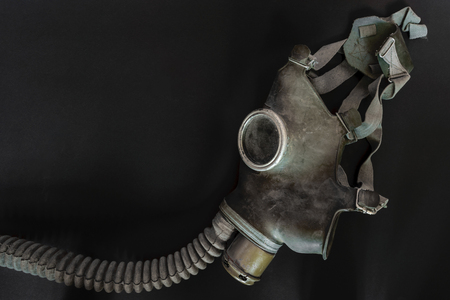 Very old gas mask on black background surface