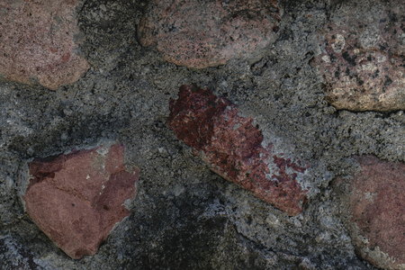 Wall made from red stones and cement background surface Фото со стока