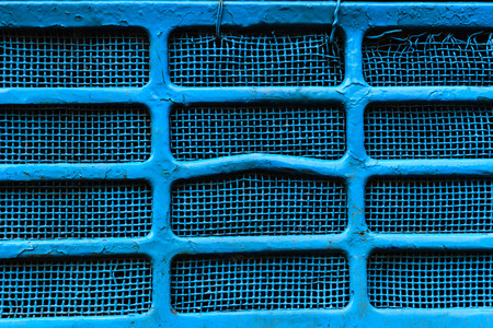 Background surface of blue, dirty and damaged metallic grid