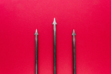 Old, rusty and metal trident with three spikes on red background surface
