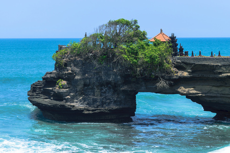 Landscape of Bali island shore with dark blue Indian ocean, huge waves and black cliff with temple