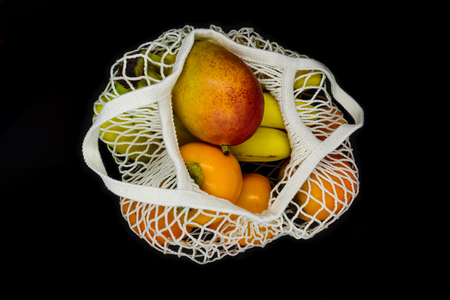 Exotic fruits in white mesh net bag and isolated on black background
