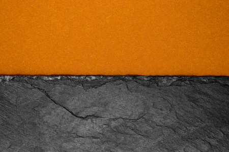 Abstract background composition of divided in the half matt dark orange color paper and black stone with copy space