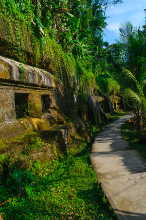 Carved in the stone ancient Gunung Kawi Temple with royal tombs illuminated by evening sun and leading path through the jungles in Bali, Indonesia