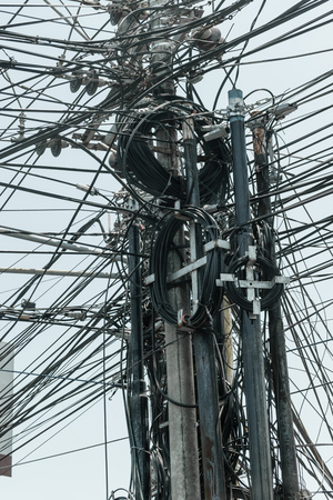 Abstract background surface of bunch of black wires connected on the pillars in Bali island, Indonesia Stock Photo