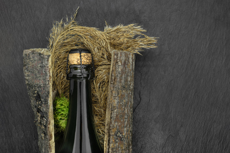 Abstract composition of closed with beige cork champagne black glass bottle placed in tree bark with bent and moss on black stone background