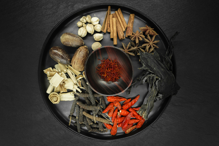 Various spices in black round bowl on black stone background. Assortment of dried spices: Saffron, black and red chilli, Lemongrass, Nutmeg, Cinnamon, Anise, Cardamom, Seaweed 写真素材