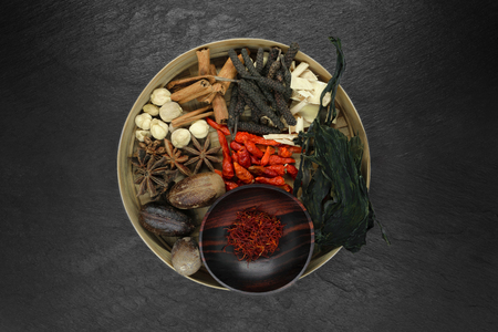 Various spices in natural bamboo bowl on black stone background. Assortment of dried spices: Saffron, black and red chilli, Lemongrass, Nutmeg, Cinnamon, Anise, Cardamom, Seaweed