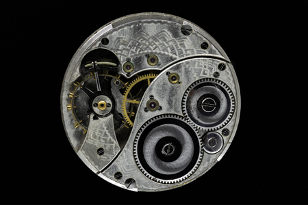 Very old, dusty and vintage hand watch mechanism isolated on black background
