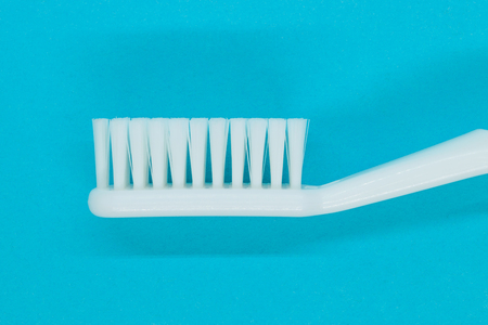 Side view of white toothbrush on blue background Stock Photo
