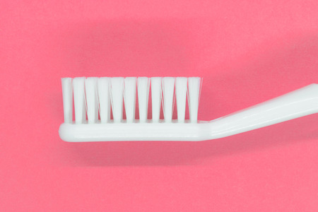 Side view of white toothbrush on pink background Stock Photo