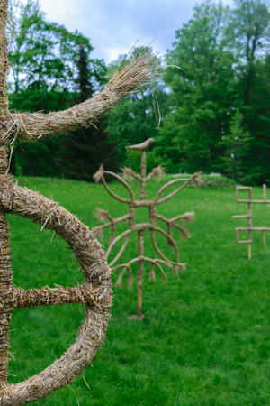 Baltic mythology gods symbols made from straws standing in the green meadow during cloudy day