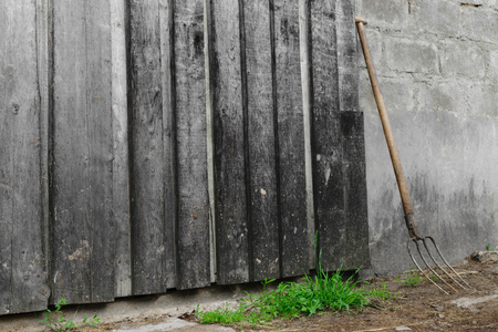 Pitchfork placed near the grey wooden and concrete barn wall Фото со стока