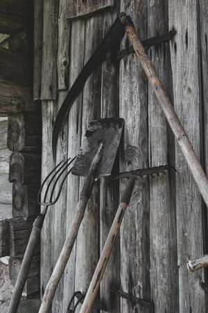 Very old, rusty and dirty garden working rural tools (hoe, scythe, spade, rake, pitchfork) near the barn wooden wall in countryside during summer time Archivio Fotografico