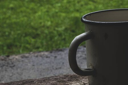 Part of very old with a lot of scratches white metallic mug in front of the green grass background nd placed on wooden plank with copy space Banco de Imagens