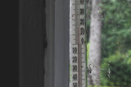 Old, dusty and surrounded with spider webs air thermometer hangs outside the window in front of the green forest with copy space