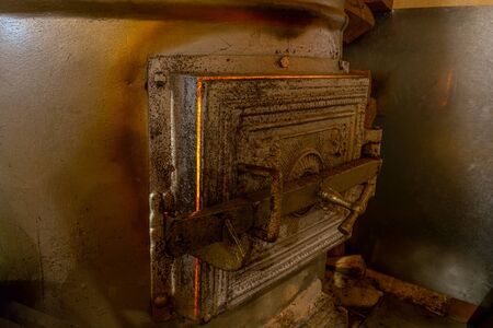 Metallic rural furnace with close doors and burning fire inside it illuminated by yellow fire light coming through it