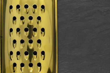 Part of golden and shiny hand grater with holes on black stone background with copy space