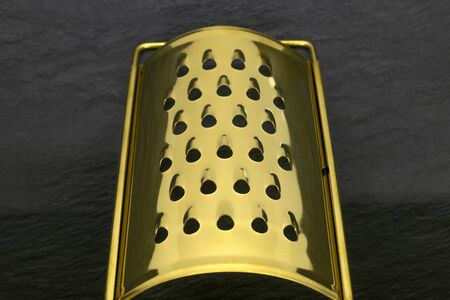 Perspective view of golden and shiny hand grater with holes on black stone background. Center of the grater is in camera focus Stockfoto