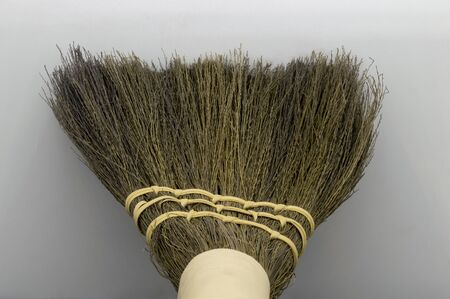 Perspective view of straw broom on grey background with copy space