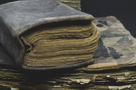 Abstract composition side view of old, aged, dusty and torn books placed on each other in front of the black background