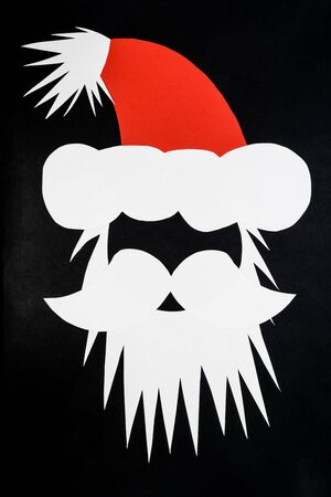 Abstract composition of Santa Claus head with cap made of white nd red paper and placed on dark black and grey background with copy space