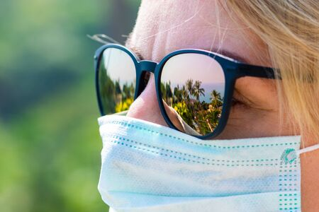 Travel and healthcare concept. Woman wearing medicine mask and sun glasses with tropical resort reflections on it to prevent virus infection on vacation 版權商用圖片