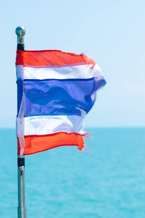 Fluttering in the wind torn Thailand flag in front of the light blue sea and sky background. Flag rod is in camera focus and the end of the flag is in motion blur