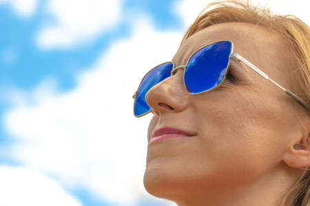 Blonde womans close-up profile face with blue sunglasses and pink lipstick in blue sky with white clouds background with copy space