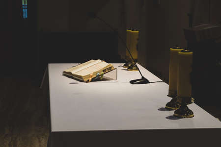 Dark church altar with open bible book and yellow candles on table with white tablecloth
