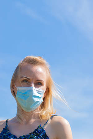 Healthcare and medicine concept. Portrait of blonde woman with windswept hair and medicine mask on her face. Woman wear blue dress in blue sky background with copy space