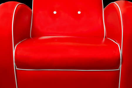 Part of luxury red armchair and white edgings isolated on black background
