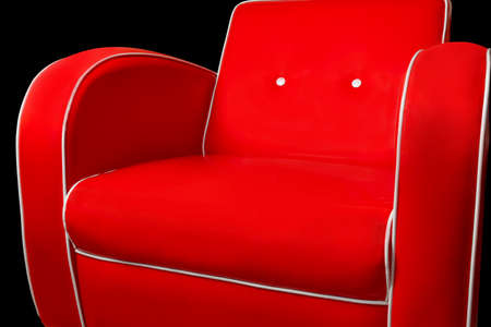 Luxury red armchair with white edgings isolated on black background