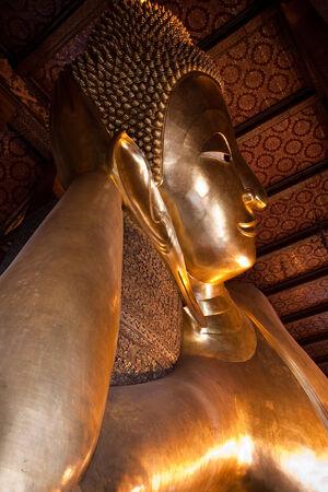 Reclining buddha in Wat Pho with half view of Bangkok, Thailand