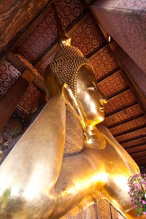 Half view of reclining buddha in Wat Pho of Bangkok, Thailand photo