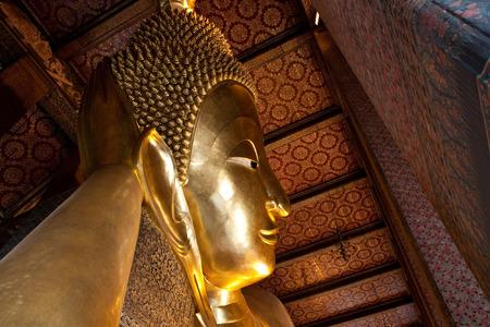 Golden buddha face in half view of Bangkok, Thailand