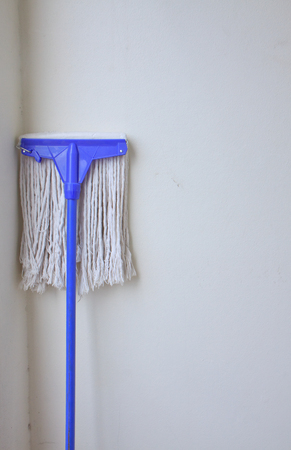 cleaness: Mop on the wall background Stock Photo