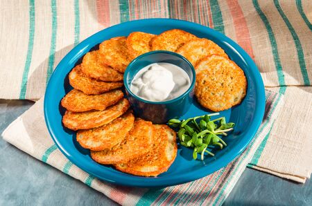 Homemade potato pancakes, latkes, draniki, hash browns or fritters served with sour cream and sunflower sprouts. Traditional Hanukkah treats. Close-up