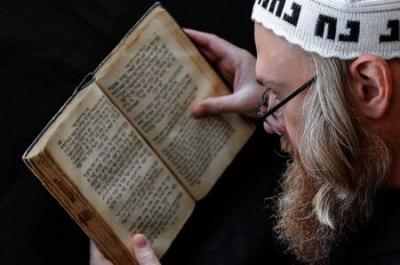 A Hasidic Jew reads Siddur. Religious orthodox Jew with a red beard and with pace in a white bale praying. On the bale is an inscription Rabbi Nahman from Uman. Close-up