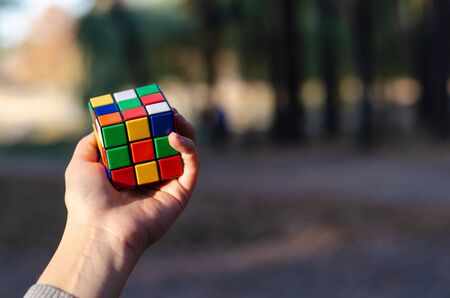 Kyiv, Ukraine - October 18, 2019. Rubiks cube in a female hand against the background of nature in the rays of the setting sun.