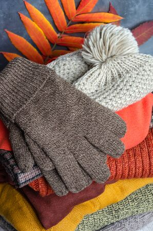 Stack of folded warm knitted women's sweaters, scarf, hat with pompom, gloves in warm colors and bright autumn leaves. Close-up Stock Photo