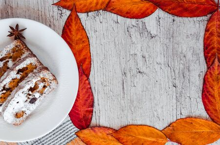 Homemade carrot cake with walnuts and dried fruits, sprinkled with powdered sugar. Frame of autumn leaves. Healthy desserts. Healthy eating concept. Copy space