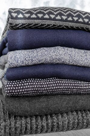 Stack of folded warm knitted men's sweaters on gray background. Close-up Stock Photo