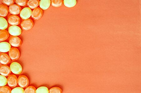 Closeup of hard sucking fruit candies on an orange background. Orange and lemon sweets. Halloween background. Copy space. Top view
